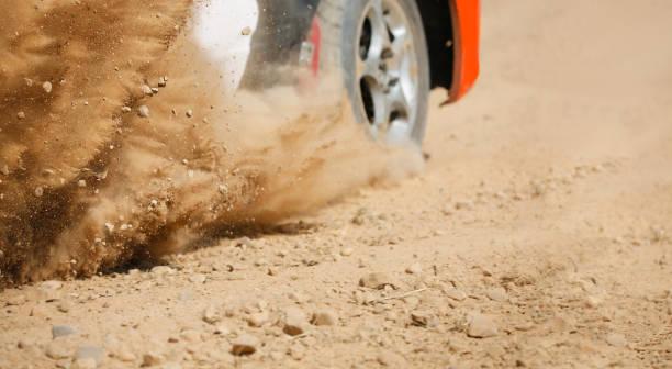 Sand spritzt von Rallye-Rennwagen auf Schotterpiste. – Foto