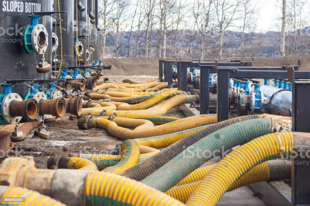 Sand tanks and hoses at a drilling well site for fracking a horizontal well. stock photo