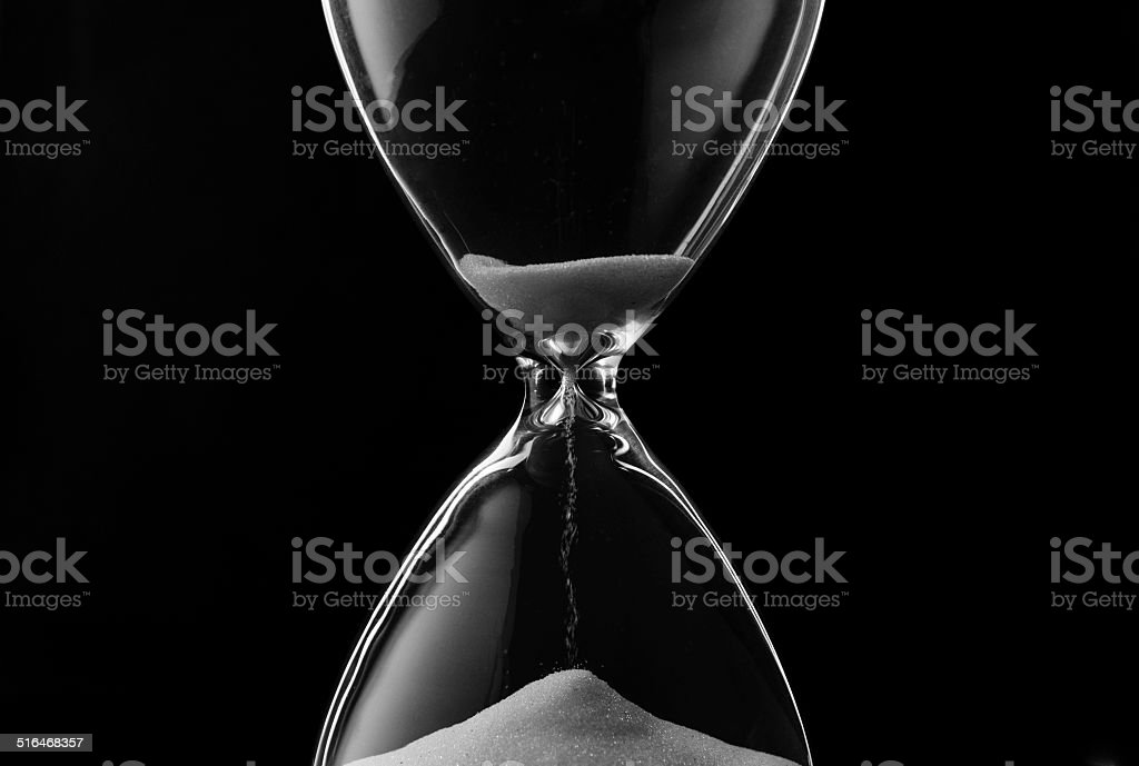 Sand trickling through the bulbs of an hourglass stock photo
