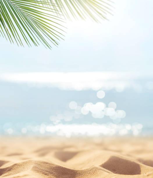 Sand mit verschwommener Palme und tropischem Strand Bokeh Hintergrund, Sommerurlaub und Reisekonzept. – Foto