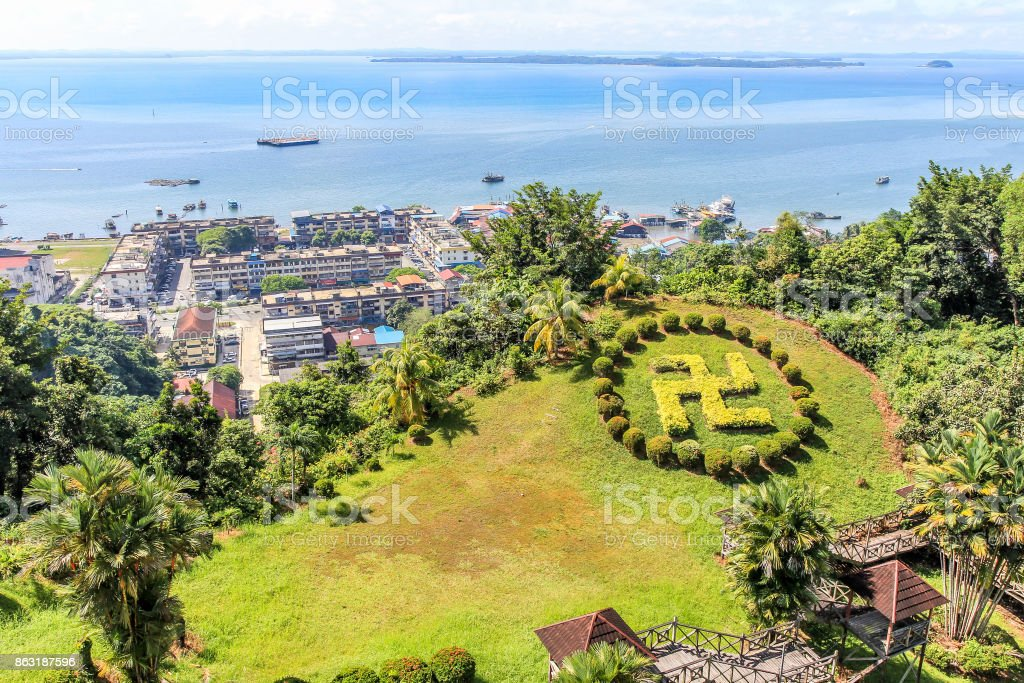 Sandakan town landscape with green lawn in Hindu counterclockwise swastika shape and blue Sulu sea in the background, Borneo, Malaysia stock photo