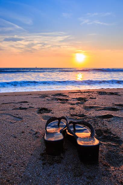 sandalen bei sonnenuntergang - salzwasser sandalen stock-fotos und bilder