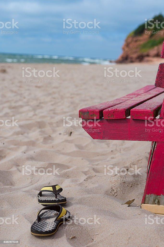 Sandals beside lifguard chair on the beach stock photo
