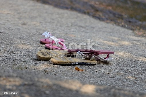 istock sandals on stone closeup 986028468