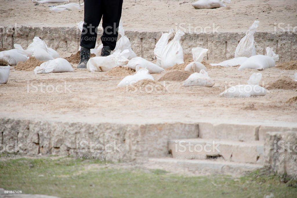 Sandbags flood prevfention and man stock photo