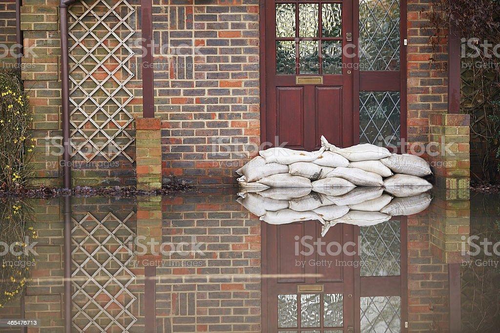 Sandbags near house door during flood stock photo