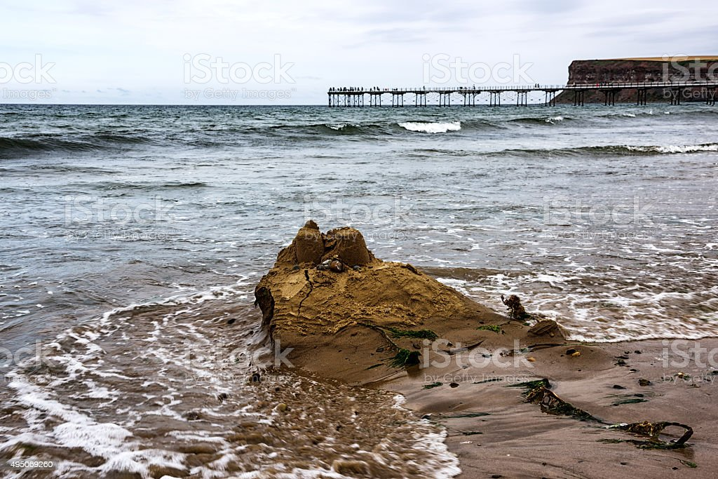 Sandcastle being washed away by  incoming tide stock photo