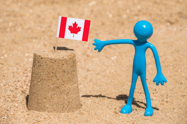 Sandcastle with Canadian flag and man figure stock photo