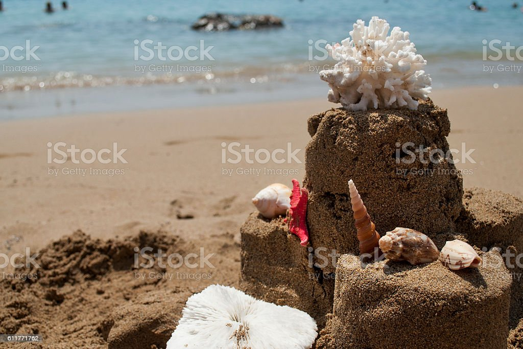 Sandcastle with starfish, coral and seashell on sandy beach stock photo