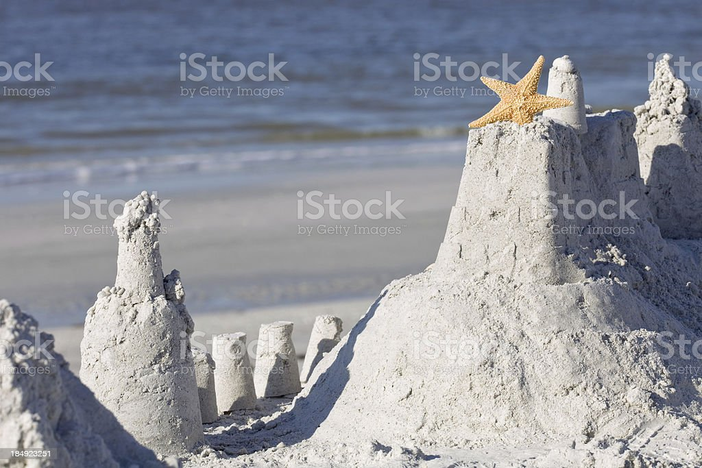 Sandcastle with Starfish on a Beach near the Ocean stock photo