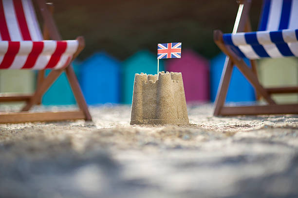 Sandcastle with UK flag between two deck chairs stock photo