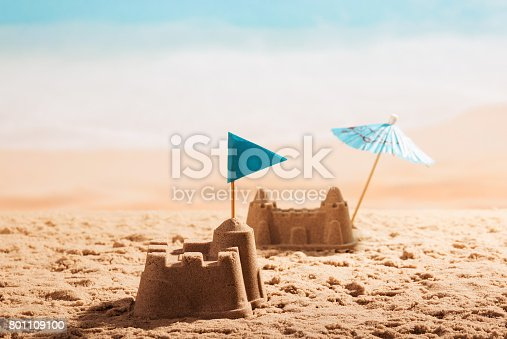 istock Sandcastles with flag and umbrella on the beach. 801109100
