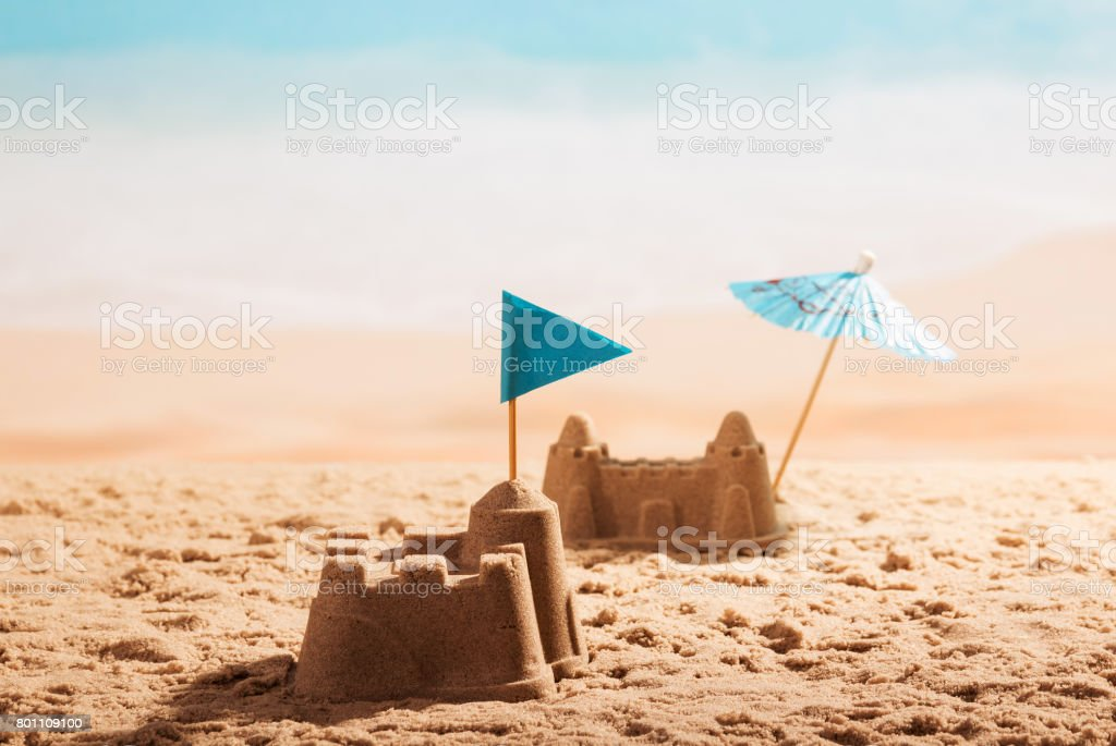 Sandcastles with flag and umbrella on the beach. stock photo