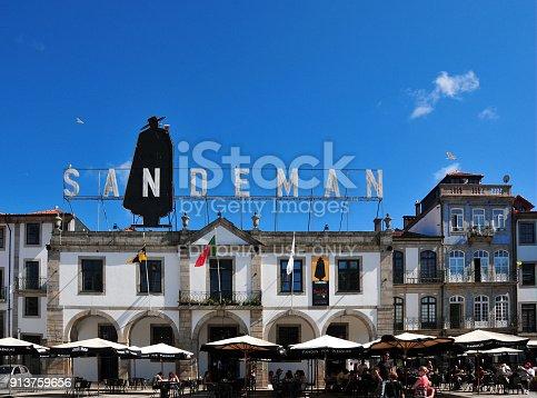 Vila Nova de Gaia, Portugal: people on a pavement café - Sandeman Port wine company building - waterfront avenue (Av. de Diogo Leite) - the brand's iconic logo features a caped man named Don, designed in 1928 by George Massiot Brown