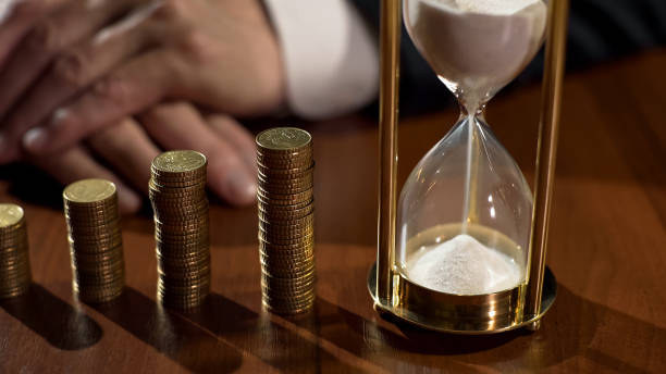 sandglass and piles of coins on table, depositor earning interest on savings - depositor stock pictures, royalty-free photos & images