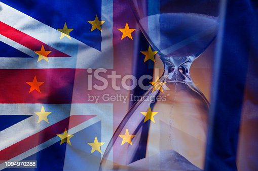 Closeup elegant sandglass counting down time to Brexit on background of overlapped flags of Great Britain and European Union