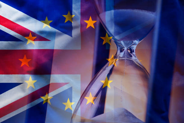 Sandglass near European and British flags Closeup elegant sandglass counting down time to Brexit on background of overlapped flags of Great Britain and European Union diplomacy stock pictures, royalty-free photos & images