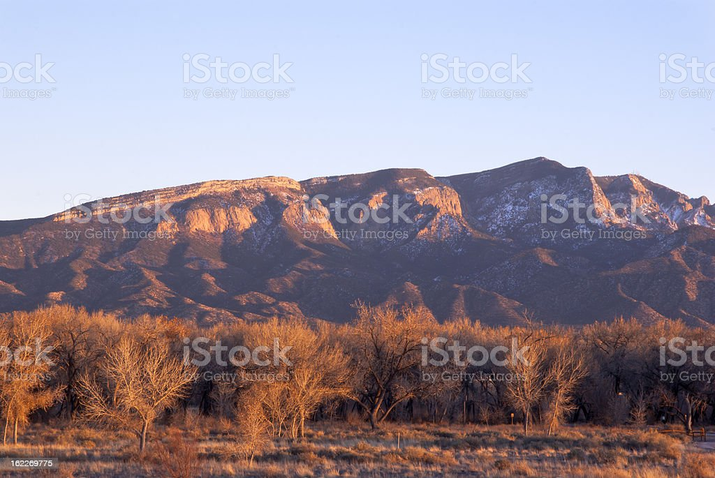 Sandia Mountains alpenglow with clear sky at sunset stock photo