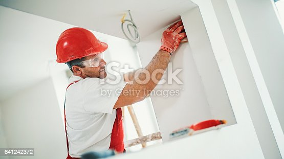 Closeup side view of a construction worker sanding a drywall and preparing it for a paint job. He's paying special attention to the corners and angles.The man is wearing red protective uniform and a red hardhat.