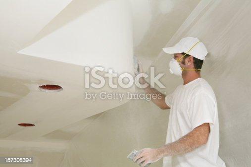 Worker sanding freshly dried sheetrock on a nice ceiling detail.