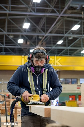 High angle view of a man in a timber factory using an industrial orbital sander to smooth some wood. He has protective clothing on. Large pieces of timber