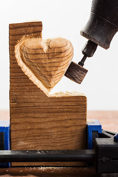 sanding wood heart, white - dremel wood stock photos and pictures