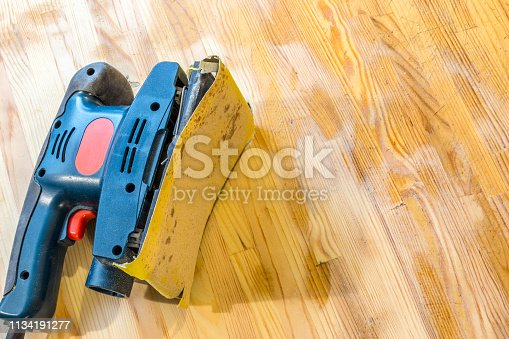 istock Sanding wood table with vibrational sander. Still life of sander laying on a table surface, partially cleaned. 1134191277