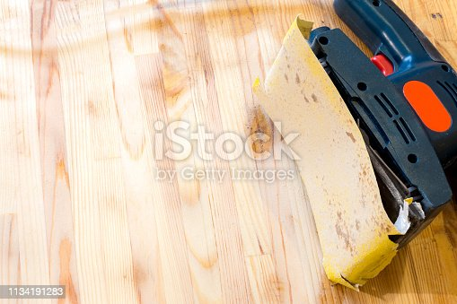 istock Sanding wood table with vibrational sander. Still life of sander laying on a table surface, partially cleaned. 1134191283