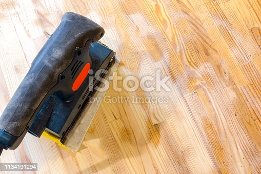 istock Sanding wood table with vibrational sander. Still life of sander laying on a table surface, partially cleaned. 1134191294