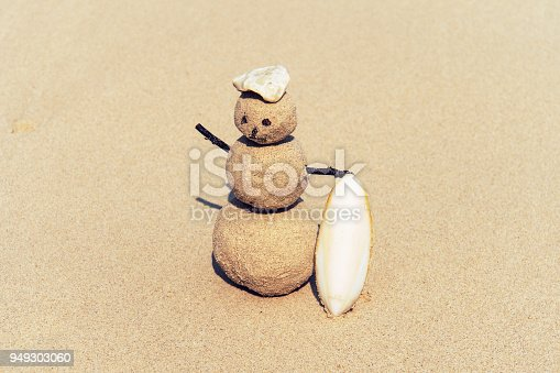 Sandman, doll from sand, snowman by the beach. joyful Sandman surfer with surfboard on sand. Christmas and new year concept on a tropical beach. Bright colors. concept of surf.