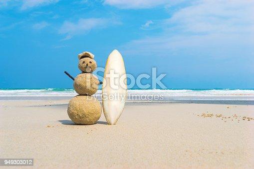 Sandman with blue sea background. Handmade yellow sand surfer holding a white surf Board on a clean beach of an exotic island. the concept of entertainment and sea travel. Vacation at sea.