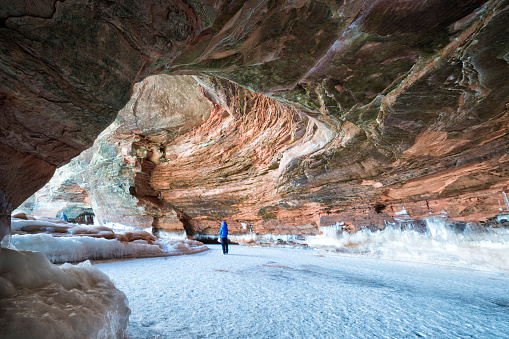 Woman walking through sandstone cavern visiting the ice caves at Apostle Island National Lakeshore, Cornucopia, Bayfield County, Wisconsin, USA