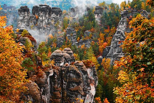 istock Sandstone rock tower in the deep autumn valley of national park Bohemian Switzerland 1014990940