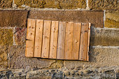 Sandstone wall with basement window and shaft for potato or coal cellar, covered with board of wooden panels, close-up