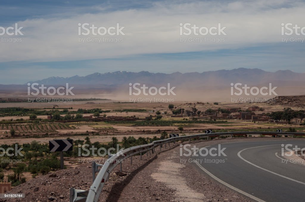 Sandstorm in valley near of High Atlas mountain range. With snow on the peaks at background. Morocco stock photo