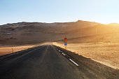 Driving in a sandstorm. Empty asphalt road through the mountains in Iceland