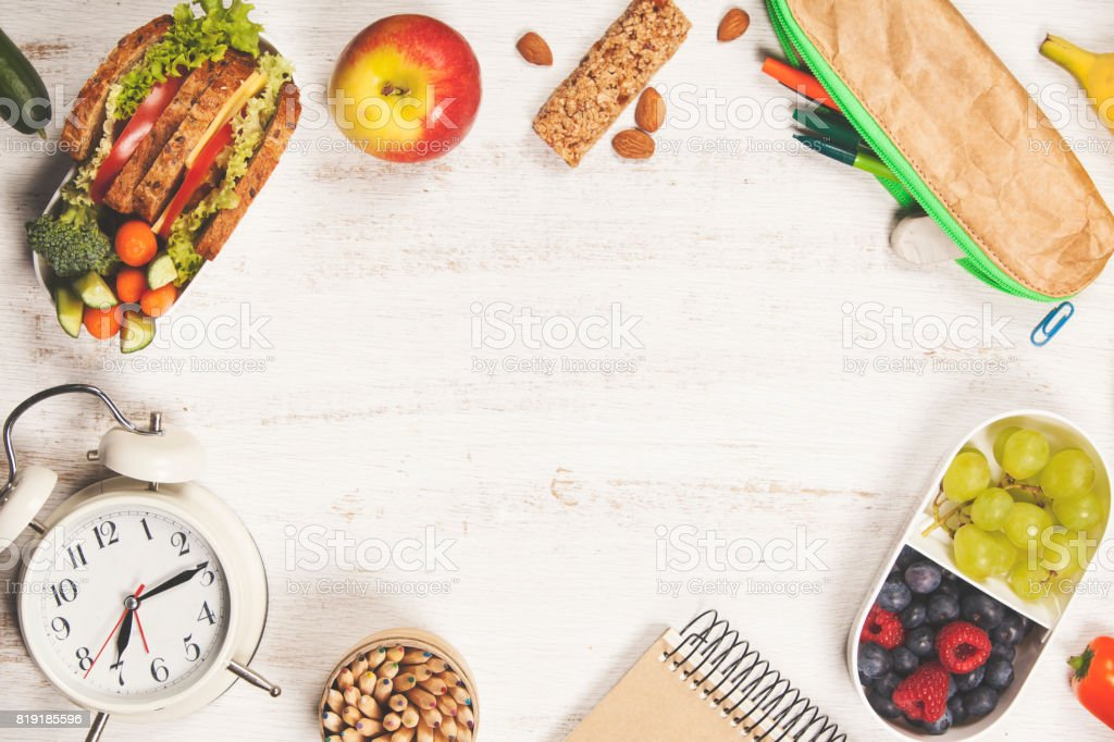 Sandwich, apple, grape, carrot, berry in plastic lunch boxes, stationery and bottle of water stock photo
