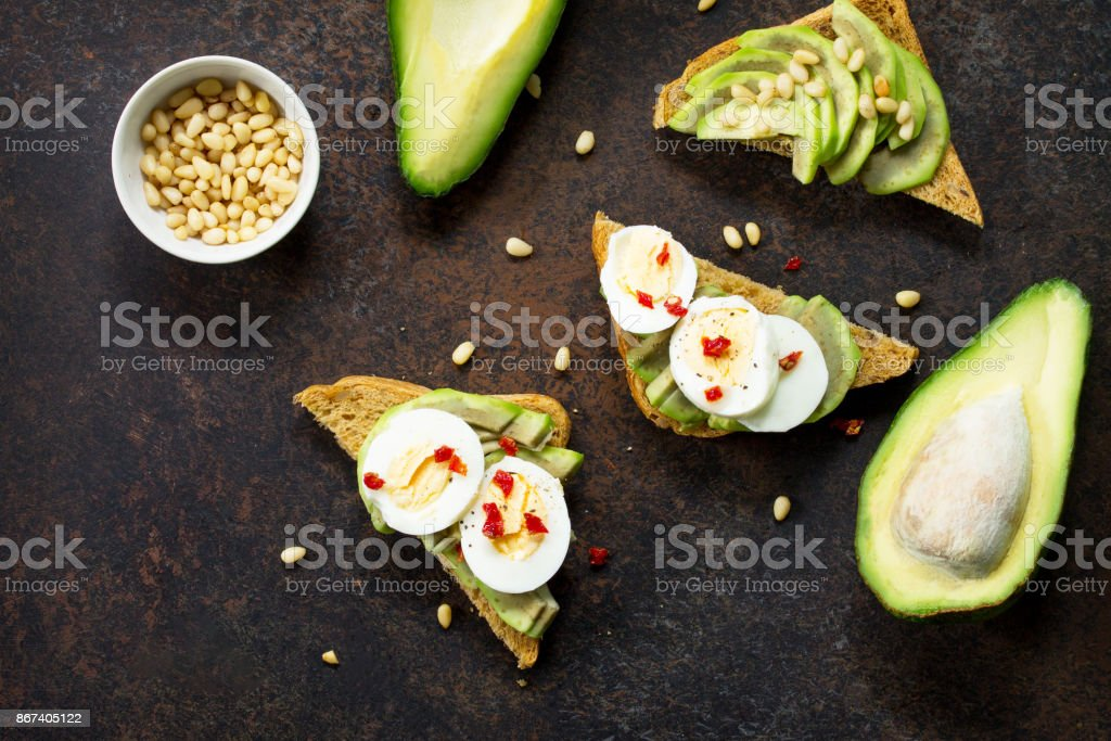 Sandwich avocado with fresh sliced avocado, egg poached and spices on a dark slate or stone background. Copy space. Flat lay, top view. stock photo
