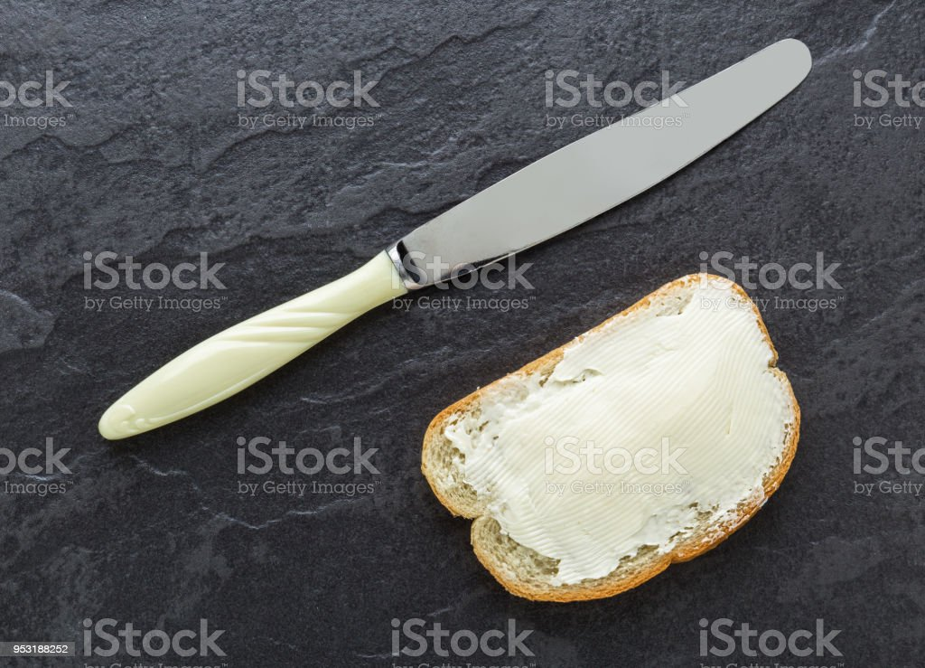 Sandwich, bread with butter and a knife on dark stone background stock photo
