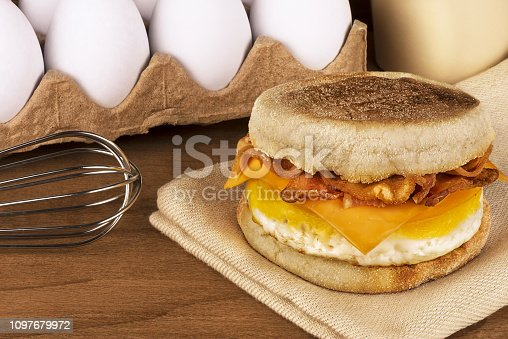 Sandwich breakfast with ingredients in background. English muffin, egg, cheese and bacon.