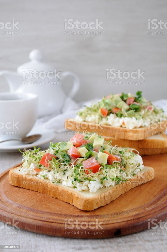 Sandwich for breakfast from tender, juicy germinated alfalfa sprouts with soft ricotta, tomato and avocado slices, with a cup of coffee or tea, which may be better for a break zbiór zdjęć royalty-free