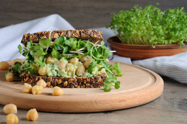 Sandwich of rye bread with cereals with crushed avocado, chickpeas and sprouts of radish shoots. Sandwich of rye bread with cereals with crushed avocado, chickpeas and sprouts of radish shoots. A great idea for those who watch their health and vegetarian. chick pea stock pictures, royalty-free photos & images