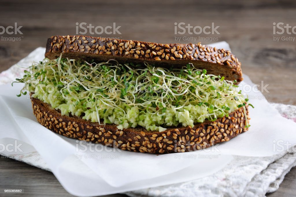 Sandwich of tender, juicy germinated alfalfa and avocado sprouts on slices of rye bread with cereals. This is a great idea for those who watch their health. royalty-free stock photo