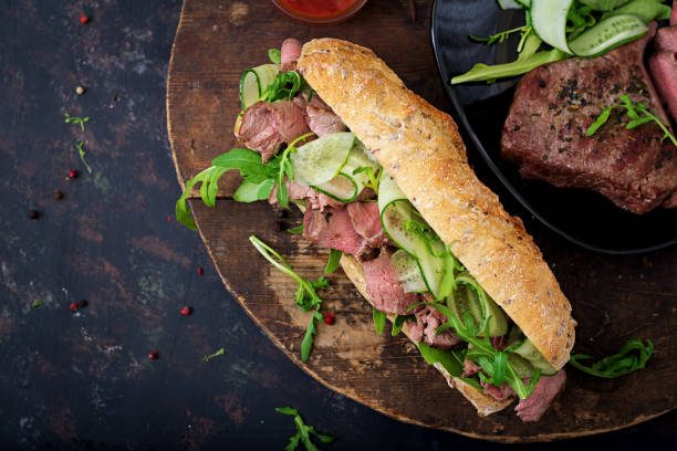 sandwich of whole wheat bread with roast beef, cucumber and arugula. top view. flat lay. - pastrami stock pictures, royalty-free photos & images