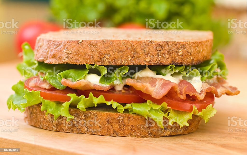 BLT sandwich on a wooden cutting board stock photo