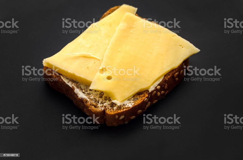 Sandwich on black bread with cheese and butter royalty-free stock photo
