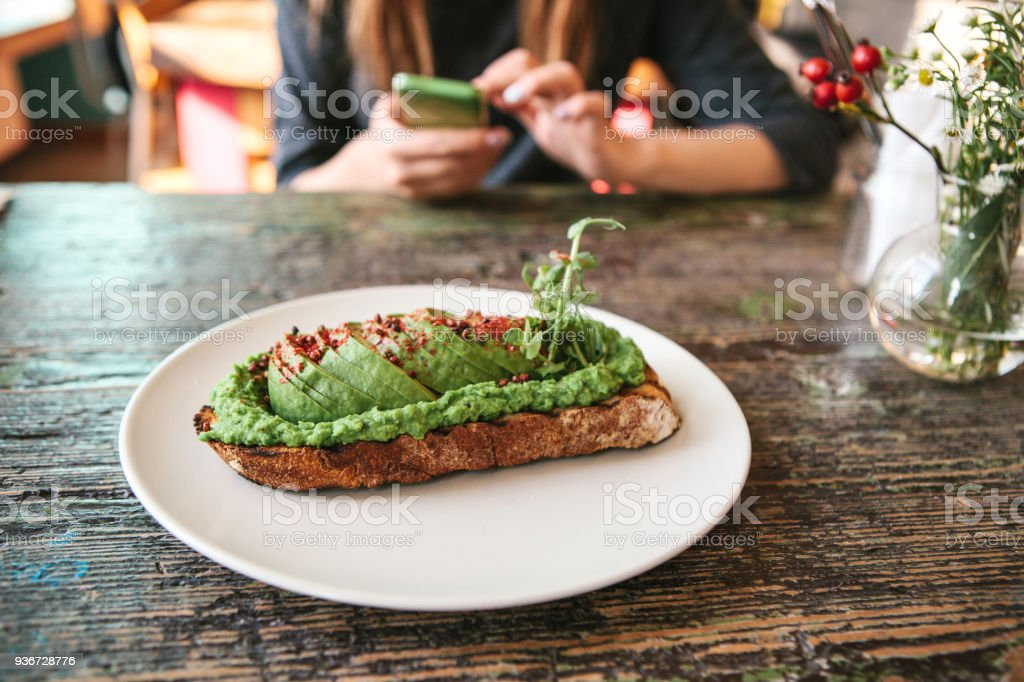 Sandwich with avacado on a wooden table. The girl is going to call or write a message to another person in the background. stock photo