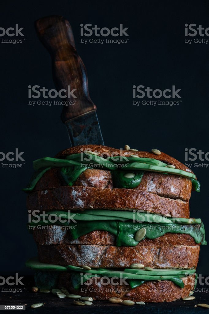 Sandwich with avocado and green pesto cheese on dark background royalty-free stock photo