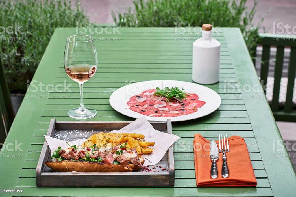 sandwich with baguette and meat on a background of a green table and a glass of pink wine and prosciutto. italian fast food royalty-free stock photo