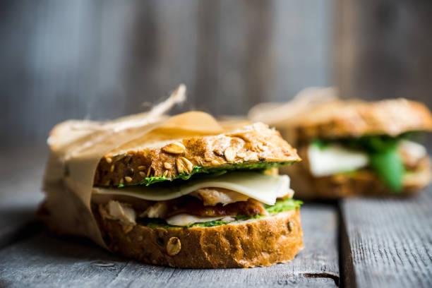 sandwich with cereal bread, chicken, pesto and cheese on the rustic wooden background - panino ripieno foto e immagini stock